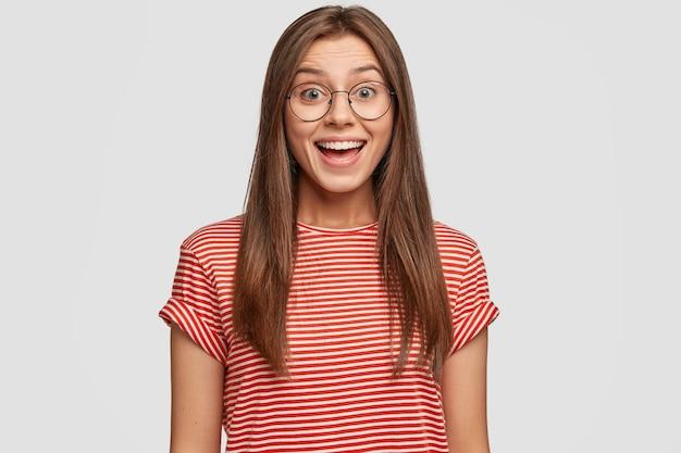 Binnen schot van tevreden brunette vrouw met donker haar, draagt ronde bril, glimlacht vreugdevol