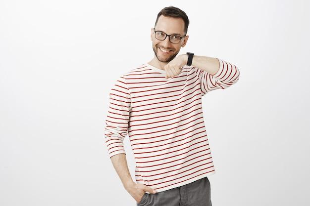 Binnen schot van tevreden gelukkig europese man met borstelharen in glazen, hand opsteken en luisteren naar geluid, tevreden zijn met de kwaliteit van het gadget