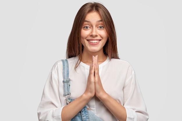 Binnen schot van tevreden knappe vrouw smeekt om genade, heeft positieve uitdrukking, zachte glimlach, houdt handpalmen in gebed gebaar