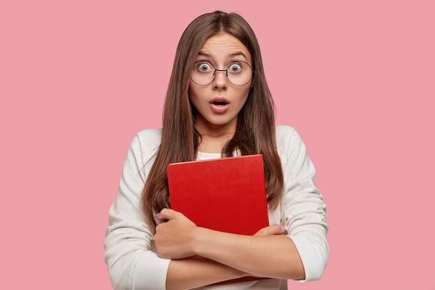 Binnen schot van verbaasd verbaasd afgeluisterd mooi schoolmeisje reageert op onverwacht nieuws, houdt rood boek vast
