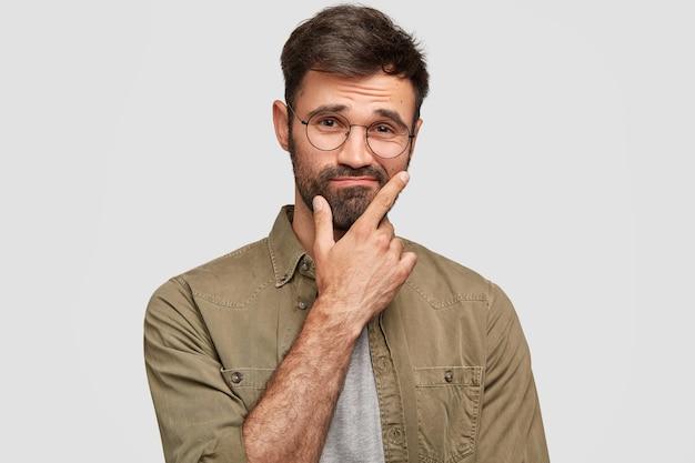 Binnen schot van verbaasde aarzelende ongeschoren man houdt kin vast en twijfelt, trekt wenkbrauwen op, heeft geen idee van uitdrukking, draagt stijlvol shirt, geïsoleerd over witte muur. mensen, emoties, levensstijlconcept