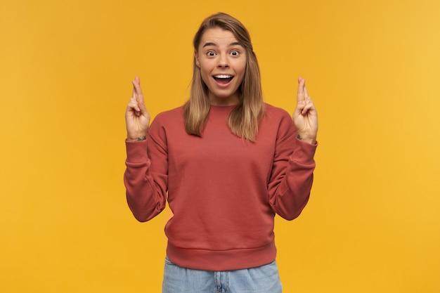 Binnen schot van verbaasde jonge gelukkige vrouw, draagt rode trui en spijkerbroek, staande