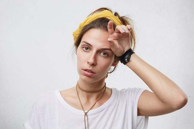 Binnen schot van vermoeide vrouw in vrijetijdskleding met haar hand op het hoofd. vermoeide huisvrouw ziet er uitgeput uit