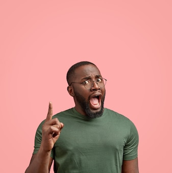 Binnen schot van verontwaardigde zwarte ongeschoren man opent mond wijd, drukt negatieve emoties uit