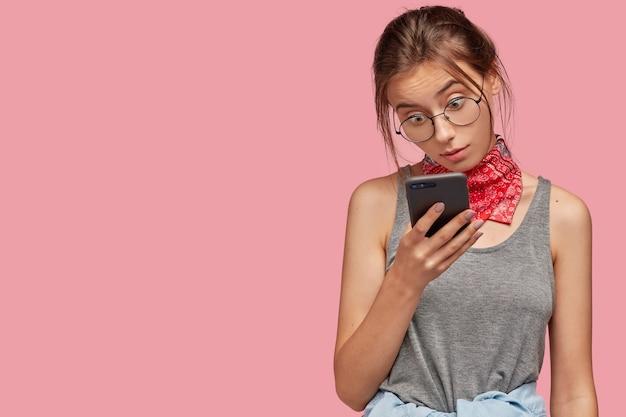Binnen schot van verrast donkerharige vrouw draagt ronde transparante bril, staart in scherm van slimme telefoon