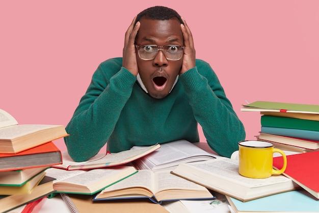 Binnen schot van verrast zwarte jongeman met bang uitdrukking, houdt mond open, overweldigd door doodsbang nieuws, leest schoolboeken, drinkt koffie