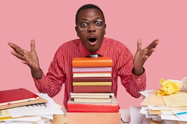 Binnen schot van verrast zwarte man spreidt handen, heeft een verbaasde uitdrukking, houdt de mond open, zit aan een bureau met een stapel schoolboeken