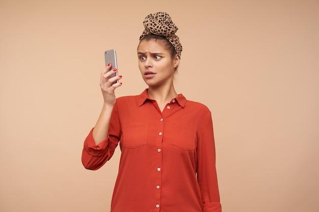 Binnen schot van verwarde jonge brunette vrouw met hoofdband in knoop terwijl poseren over beige muur, mobiele telefoon in opgeheven hand houden en verward op het scherm kijken
