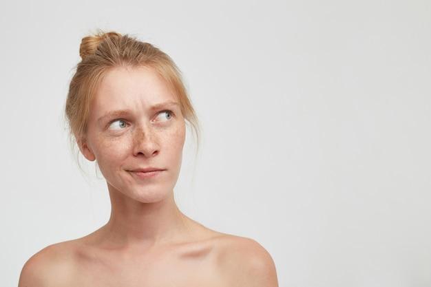 Binnen schot van verwarde jonge mooie dame die haar foxy haar in knoop draagt terwijl ze op een witte achtergrond staat, bedachtzaam opzij kijkend met gevouwen lippen