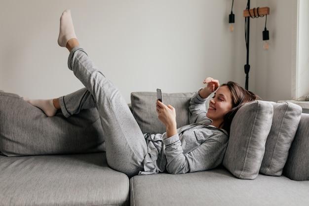 Binnen schot van volledige lengte van gelukkige vrouw in huiskleren die smartphone scrollen terwijl zij op de bus in zonnige dag ligt.