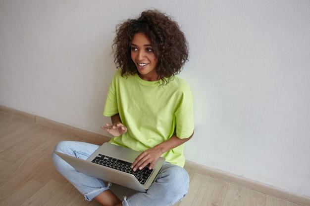 Binnen schot van vrij donkerharige gekrulde vrouw zittend op de vloer met laptop en op zoek naar persoon achter de schermen, glimlachend en gebaren met de hand
