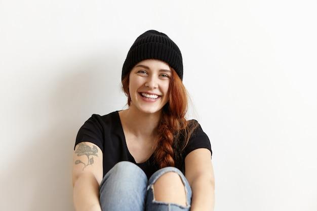Binnen schot van vrolijk jong hipstermeisje met gemberhaar in vlecht en tatoegering die op vloer rusten