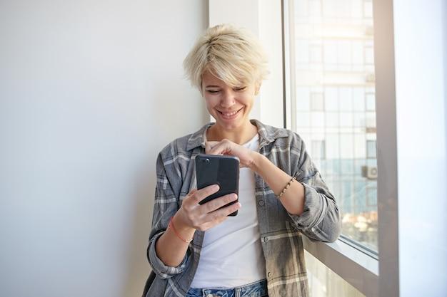 Binnen schot van vrolijke jonge dame met blond kort haar, het dragen van vrijetijdskleding, leunend op venster een kijken op de telefoon in haar hand met een brede glimlach