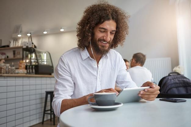 Binnen schot van vrolijke jonge man met baard en krullend bruin haar poseren boven café interieur, luisteren naar muziek en chatten met vrienden terwijl het hebben van een kopje koffie