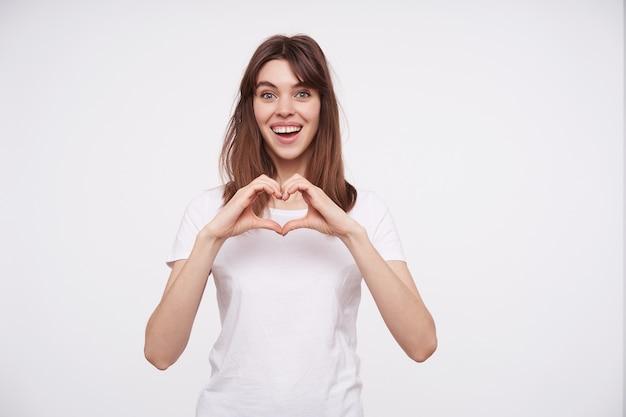 Binnen schot van vrolijke jonge mooie donkerharige vrouw die hart met opgeheven handen vouwt en vreugdevol kijkt met een brede oprechte glimlach, geïsoleerd over witte muur