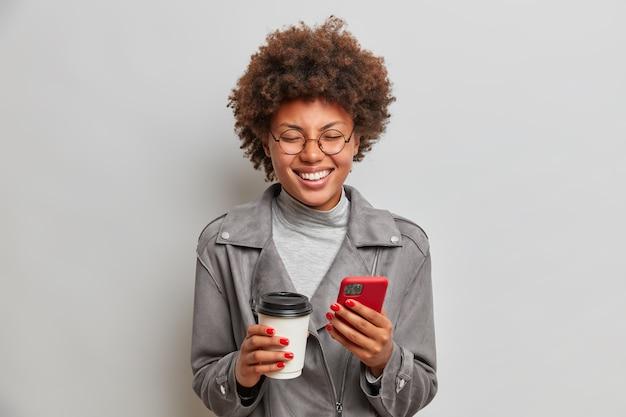 Binnen schot van vrolijke optimistische vrouw barst in lachen uit, drinkt koffie om te gaan, mobiele telefoon in handen houdt, wacht op iemand, loopt overdag, drukt positieve emoties uit