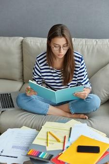 Binnen schot van vrouw freelancer gericht in boek, zit in lotus houding op comfortabele bank, omringd met papieren, werkt vanuit huis, registreert informatie uit het netwerk, bereidt zich voor op eindexamen