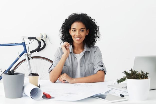 Binnen taille portret van vrolijke, zelfbepaalde jonge vrouw ingenieur gelukkig gevoel