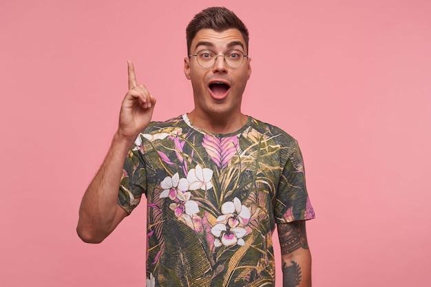 Binnen verrast knappe tatooed jonge man in casual stijl t-shirt staan met verbaasd gezicht, kijken met idee teken, geïsoleerd
