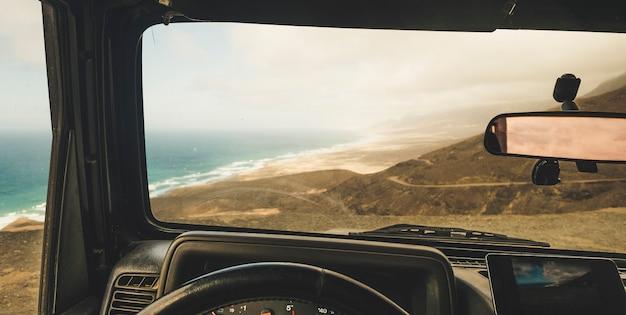 Binnenaanzicht van auto met mobiel modern telefoon-gps-systeem om de weg te vinden en kaarten te gebruiken op een schilderachtige plek buiten de weg met uitzicht op het strand en de bergen