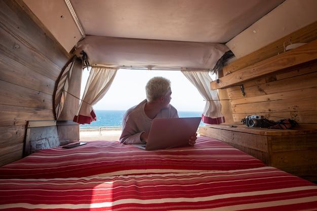 Binnenaanzicht van een minibus met een jonge blonde man die zijn laptop gebruikt en in de buurt van het strand en de zee werkt - levensstijl van reizigers en nomaden die plezier hebben