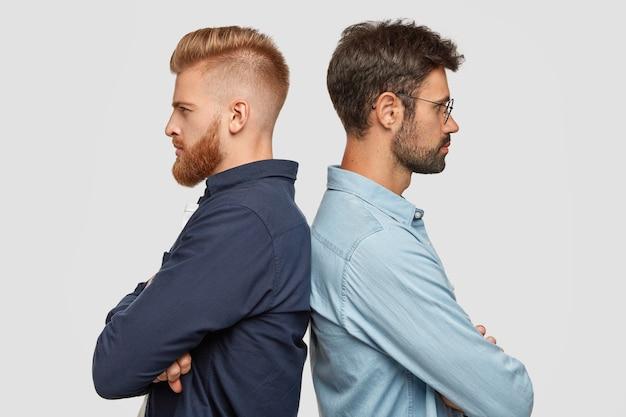 Binnenaanzicht van serieuze twee partners staan achter, hebben wat onenigheid, houdt de handen gevouwen