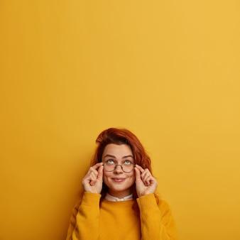 Binnenbeeld van doordachte roodharige blanke vrouw houdt handen op brilmontuur, probeert iets hierboven te zien, heeft een nieuwsgierige blije uitdrukking
