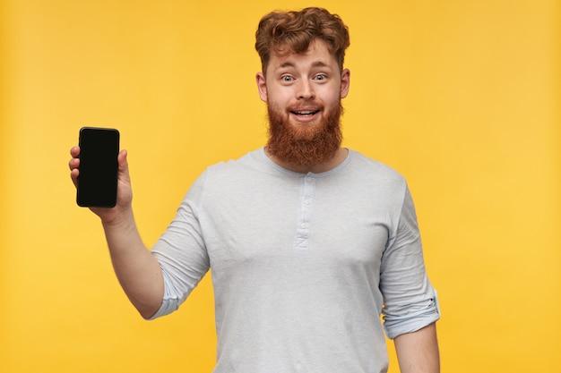 Binnenbeeld van jonge man met grote baard, glimlacht breed en toont weergave van zijn telefoon met een lege zwarte exemplaarruimte op geel