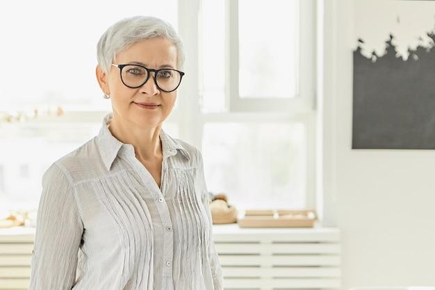 Binnenbeeld van modieuze elegante volwassen europese vrouw met kort grijs pixiekapsel met het gelukkige glimlach stellen