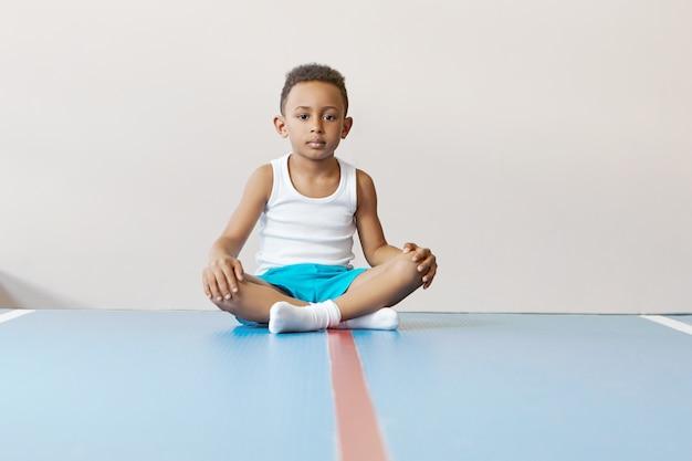 Binnenbeeld van zelfbepaalde knappe afrikaanse schooljongen die in sportkleding de benen gekruist houdt