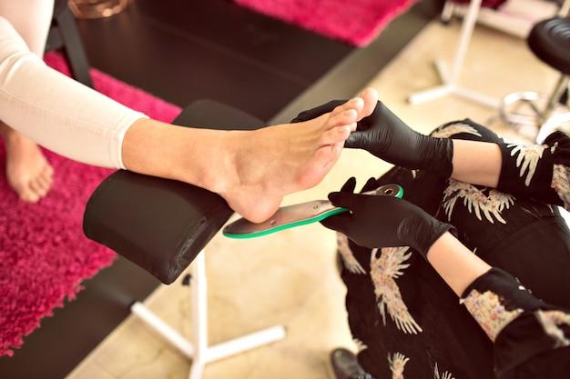 Binnenfoto in schoonheidssalon, een vrouw die pedicure maakt aan de andere, werknemer in de schoonheidsindustrie, details van de nageldienst. afgezwakt kleuren, manicure bezetting.