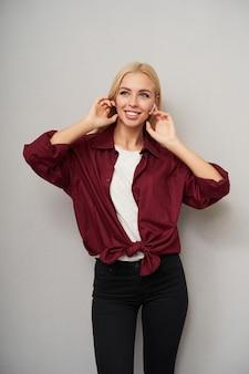 Binnenfoto van aangenaam uitziende slanke jonge vrouw met lang blond haar oortelefoons in haar oren plaatsen en oprecht glimlachen, gekleed in vrijetijdskleding over lichtgrijze achtergrond