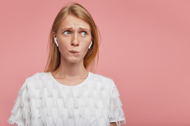 Binnenfoto van aantrekkelijke jonge vrouw met natuurlijke make-up die op haar lippen bijt en wenkbrauwen fronst terwijl ze zorgelijk opzij kijkt, staande over roze achtergrond