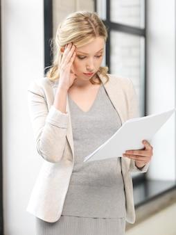 Binnenfoto van bezorgde vrouw met documenten