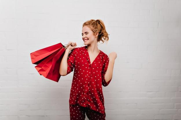 Binnenfoto van blije blanke vrouw in pyjama poseren met heden. charmant meisje in rood nachtkostuum lachen en houden papieren zak.