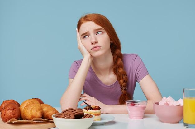 Binnenfoto van droevig roodharig meisje dat over voedsel, gezondheid, dieet, extra calorieën, bakselproducten en vers fruit denkt