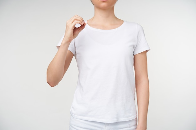 Binnenfoto van een jonge blonde vrouw die een cirkel vormt met haar vinger terwijl ze het alfabet van de dood leert, waarbij de letter o wordt weergegeven terwijl ze poseren op een witte achtergrond