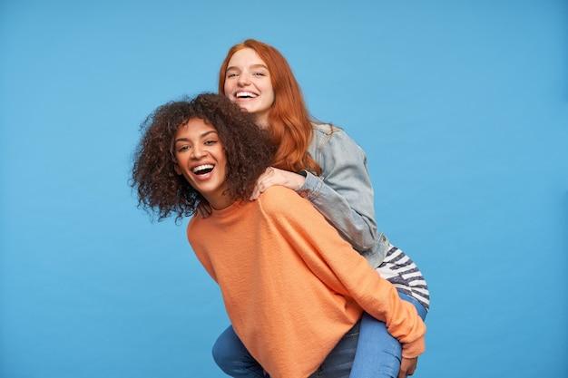 Binnenfoto van gelukkige jonge mooie dames die zich verheugen en breed glimlachen terwijl ze kijken, in een opgewekte stemming zijn terwijl ze poseren over de blauwe muur
