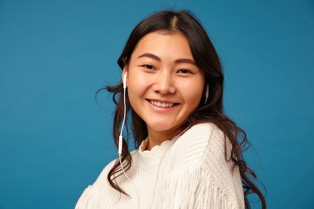 Binnenfoto van jonge bruinharige aziatische vrouw met krullen die in een goede bui zijn
