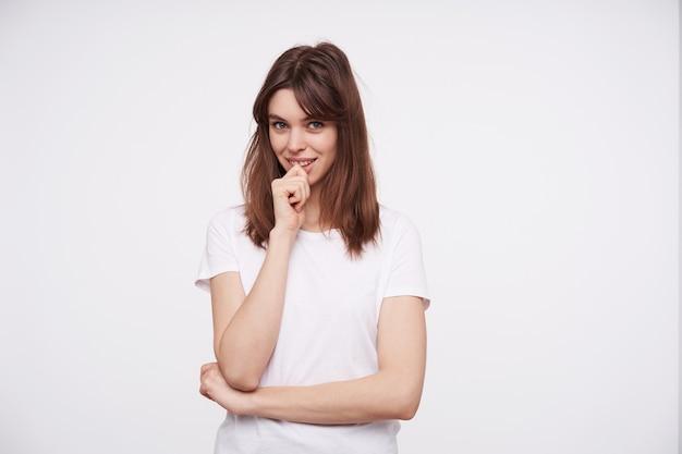 Binnenfoto van jonge charmante brunette vrouw die haar kin met opgeheven hand houdt en positief kijkt met een lichte glimlach, staande tegen een witte muur