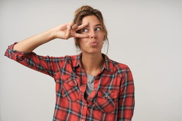 Binnenfoto van jonge grappige mooie bruinharige vrouw die gezichten trekt terwijl ze voor de gek houdt en het overwinningsteken opheft, geïsoleerd tegen een witte achtergrond