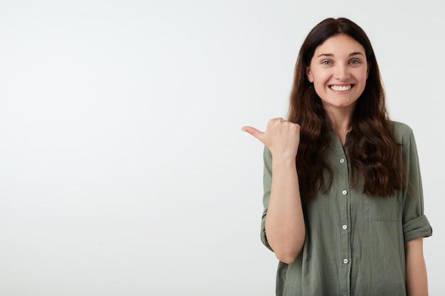 Binnenfoto van jonge mooie donkerbruine vrouw die haar duim omhoog houdt
