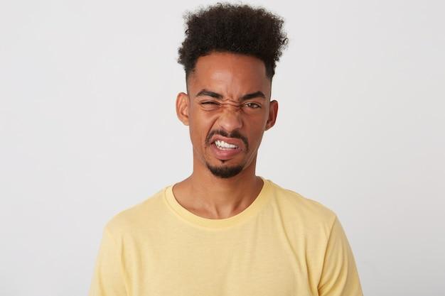 Binnenfoto van jonge ontevreden donkerbruine kerel met trendy kapsel die zijn tanden laat zien