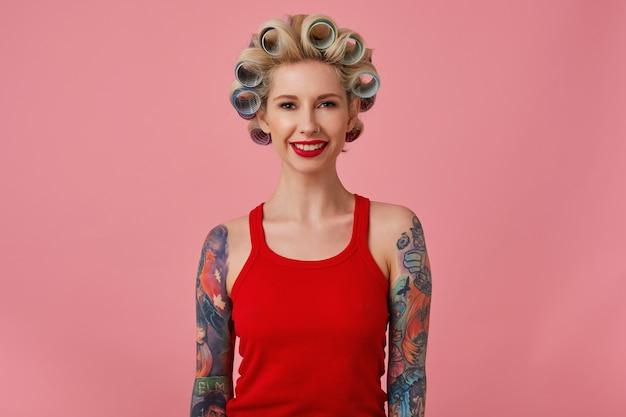 Binnenfoto van jonge positieve mooie blonde vrouw met tattooes met krulspelden op haar hoofd terwijl ze over roze achtergrond staat, feestelijke make-up draagt en zich voorbereiden op avond uitgaan