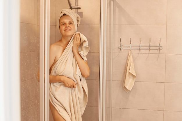 Binnenfoto van jonge volwassen slanke aantrekkelijke vrouw die uit de douche stapt, staat en het lichaam afdroogt met een handdoek, camera kijkend met positieve emoties.