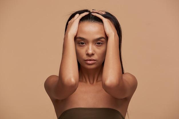 Binnenfoto van kaukasisch meisje dat haar hoofd met haar handen houdt
