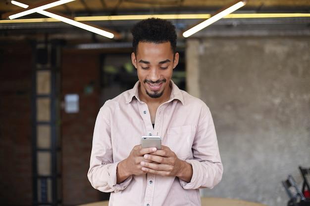Binnenfoto van knappe lachende donkere man met baard die boven de coworking-ruimte staat en smartphone vasthoudt, positief naar het scherm kijkend tijdens het chatten met zijn vrienden