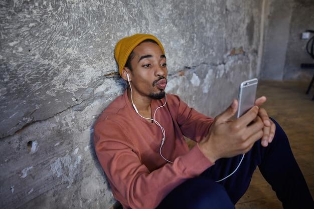 Binnenfoto van mooie bebaarde donkere man in roze trui, blauwe broek, broek en mosterdpet leunend op betonnen muur, foto van zichzelf maken met mobiele telefoon en lippen vouwen in luchtkus