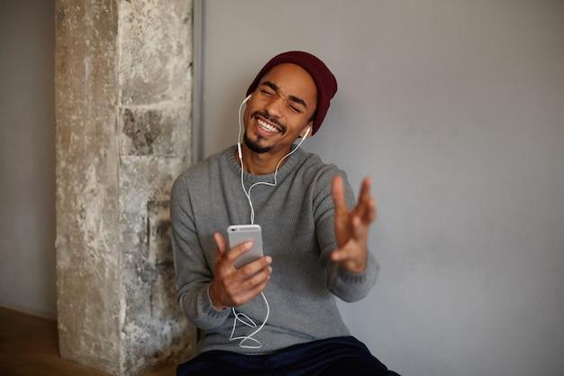 Binnenfoto van mooie jonge, bebaarde donkere man die zich voordeed op een witte muur en geniet van muziektrack, de palm emotioneel opheft tijdens het zingen met gesloten ogen
