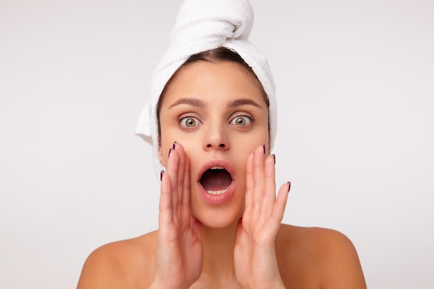 Binnenfoto van mooie jonge donkerharige vrouw poseren op witte achtergrond met badhanddoek op haar hoofd, camera kijken met grote ogen geopend en iets schreeuwen